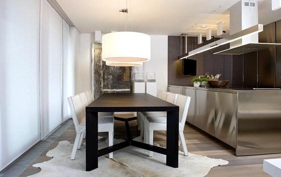 Jídelně dominuje velký jídelní stůl s koženými židlemi a originální olejové