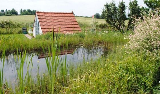 Pohled přes koupací biotop na multifunkční zahradní domek, který přímo navazuje