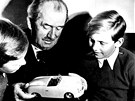 Ferdinand Porsche ukazuje vnoučatům jeden z modelů aut.