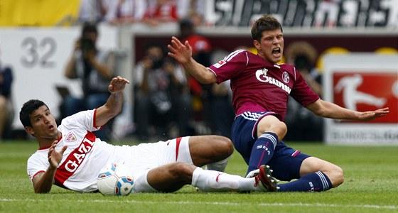 Fotbalista Maza ze Stuttgartu skluzem atakuje Klaase-Jana Huntelaara ze Schalke.