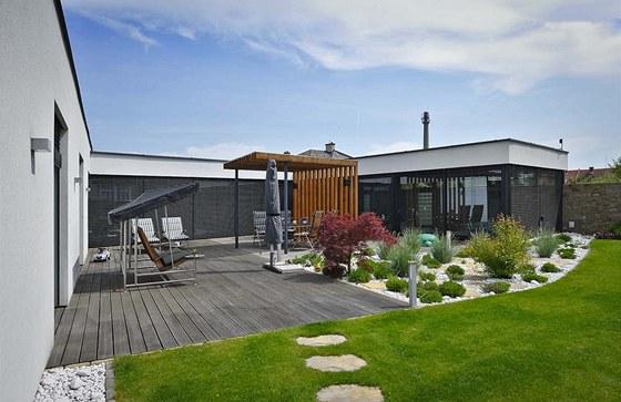 Protipólem hlavní obývací části je bazén s plochou střechou. Prosklené plochy