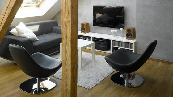Obývací prostor s trojicí střešních oken. Povrch stěny s televizí tvoří