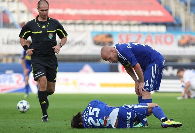 ZRAN�NÍ. Olomoucký fotbalista Jan Navrátil se svíjí na trávníku, sklání se nad