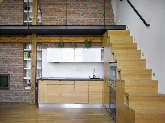 Schody integrované do kuchy�ské linky vytvá�í zajímavý výtvarný prvek v