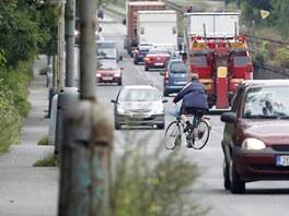 Úzká a zarostlá cyklostezka svádí kolaře k vjíždění na silnici.