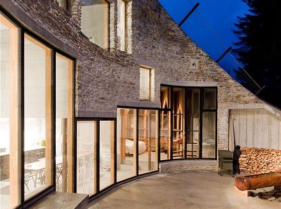 Prosklená stěna domu vede na terasu.