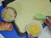 Povrch těsta potřete zlehka rozšlehaným vejcem a posypte hustě mandlovými
