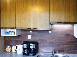 Kvůli omezenému rozpočtu použili majitelé mezi skříňky levnou plovoucí podlahu.