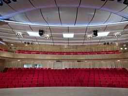 Dřevěný podvěšený akustický strop je v perlově bílé barvě,