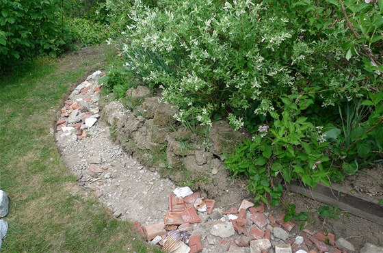 Podklad připravený pro stavbu zídky, vytvořený z úlomků kamenů, cihel, střešní