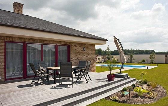 Dřevěná terasa ve vnitřním nároží plynule navazuje na úroveň podlahy v obývacím