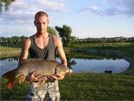 Jeden z návštěvníků Kaprodromu se svým úlovkem, v pozadí jeden z rybníků.