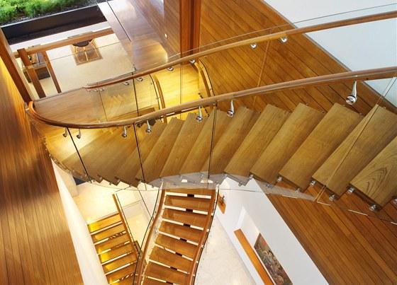 Spojnicí celého domu je dřevěné schodiště s proskleným zábradlím.