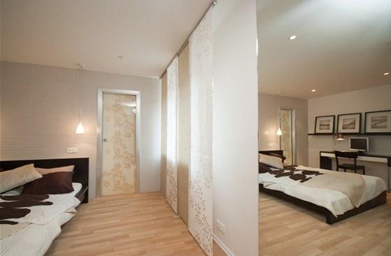 Velké zrcadlo hned za dveřmi ložnici opticky zvětšuje.
