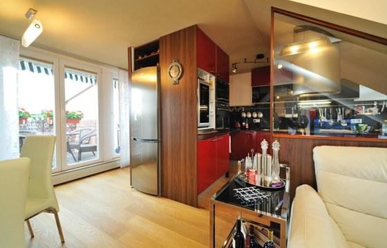 Sklo, za nímž je varná deska, odděluje kuchyňskou část od obýváku.
