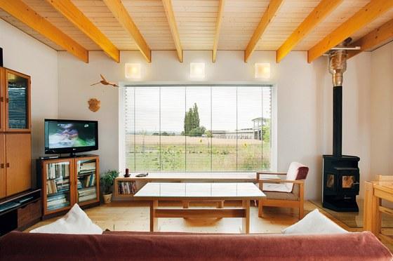 Obývací pokoj zabydlel světlý nábytek a krbová kamna.