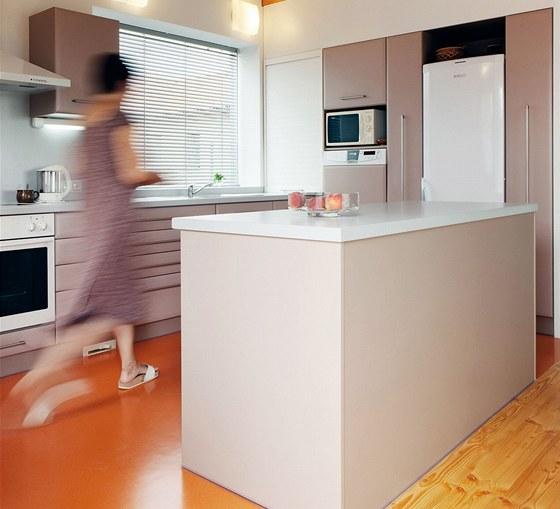 Světlá kuchyňská sestava, částečně vestavěná v nice, působí vzdušně a prostorně.