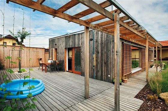 Dřevostavba s plochou střechou působí na okolí přirozeně a neokázale