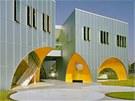 Vnitřek podloubí je zalitý jasnou oranžovou barvou, povrch budovy je kovový a
