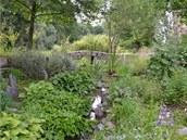 Za můstkem už se zrcadlí hladiny rybníků, na ně dál navazují svěží louky s