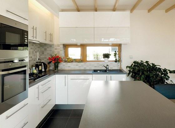 Kuchyně je od jídelny oddělena pouze opticky úložnými prostory s pracovní