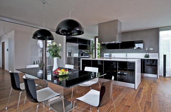 Lesklé plochy kuchyně a přilehlé jídelny se skvěle doplňují s dřevěnou