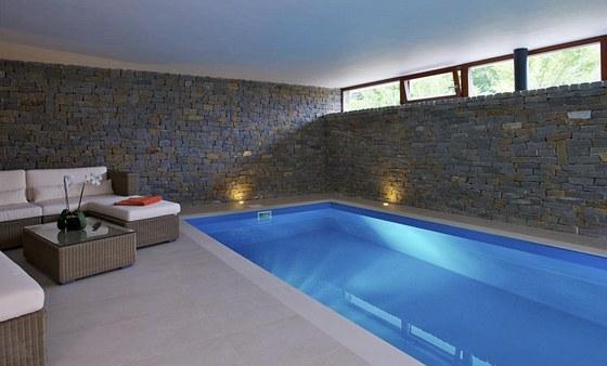 V přízemí je místnost s bazénem, saunou, posilovacím strojem Power Plate a