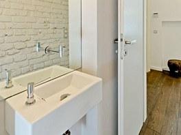 Prostor WC zvětšuje velké zrcadlo.