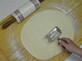 Vykynuté těsto vyklopte na pomoučený vál, vypracujte z něj plát a rozdělte jej