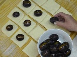 Do každého čtverce uložte po jedné švestce s cukrovou náplní, pak rohy čtverce