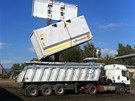 Materi�l z ostravsk�ch lagun vysyp�v� naklada� z hermeticky uzav�en�ch kontejner� do n�kladn�ch aut kryt�ch plachtami. Denn� takto vylo�� b�hem 10 hodin vlak o 22 vagonech, tedy 66 kontejner� o celkov� v�ze 1 350 tun.