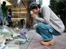 Satoko Sakaiová se modlí před obchodem Shibuya Apple v centru Tokia. (6. října