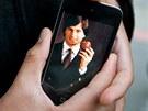 Fred Velez ze San Franciska drží iPhone s portrétem Steva Jobse. (6. října 2011)