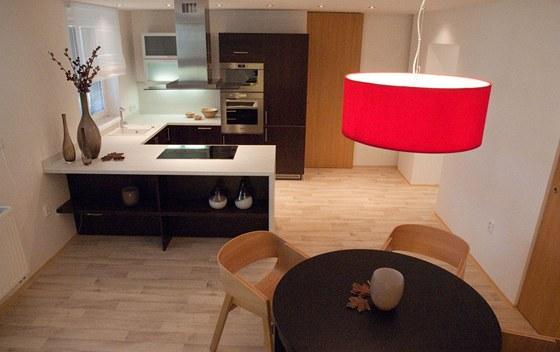 Kulatý jídelní stůl ladí tvarem jak s lustrem, tak s oblými židlemi Merano.