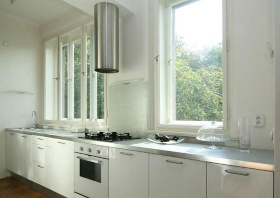Bílá moderní kuchyň částečně zasahuje do obývací pokoje zařízeného starožitným