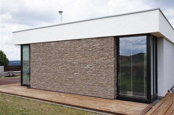 Hladká omítka a části fasády s páskovým kamenným obkladem vytvářejí zajímavý
