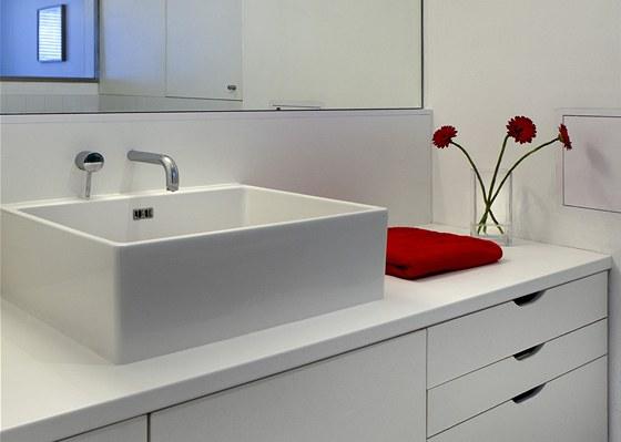 Skříně v koupelně mají stejně jako kuchyňská sestava čistě bílou barvu, takže splývají se stěnami a člověk je nevnímá jako nábytek.