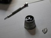 Klasické hodinářské propriety: Lupa a šroubovák. Vpravo část strojku.