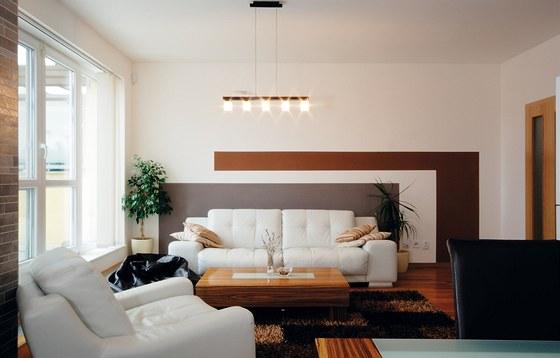 Šedá barva za světlou sedačkou vytváří kontrastní pozadí, v obýváku je šedá