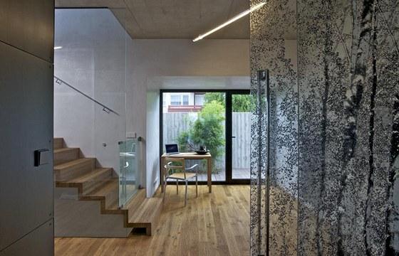 Dubové schodiště k ložnici uzavírá na levé straně stěna z kaleného skla.