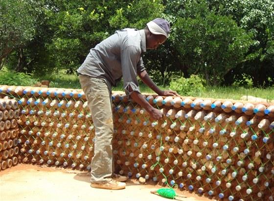 Po postavení stěny je hrdlo každé lahve omotané provázkem a propojené s hrdlem
