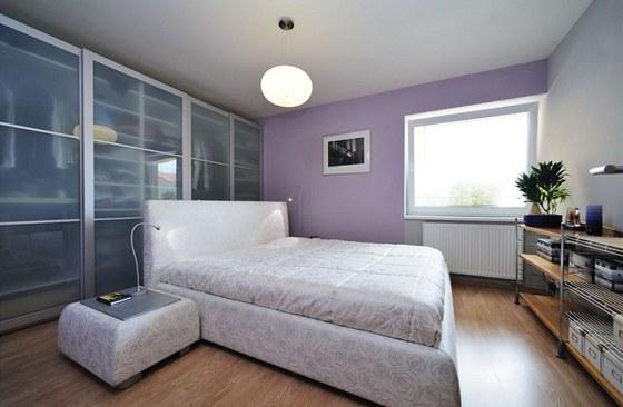 Postel je netradičně umístěná do prostoru, aby se do pokoje vešla velká sestava