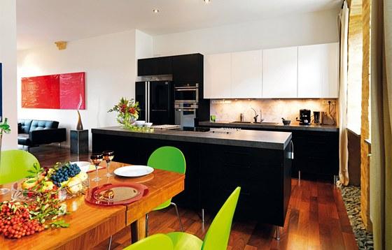 Otevřená kuchyně s ostrůvkem je vybavena americkou lednicí v černé barvě.