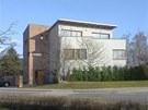 Západní přístavba se zkosenou fasádou a přesahující střechou dodává střízlivé