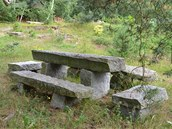 Posezení u kamenného stolu přímo nad lomem. Les v těchto místech přechází volně