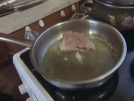 Rozpustíme máslo a osoleného a opepřeného kapra opečeme.