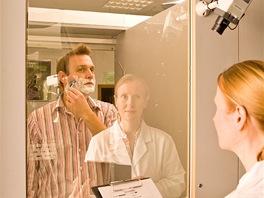 Během holení před polopropustným (jednosměrným) zrcadlem na postup dohlíží jak