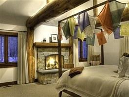 Ložnice s budhistickými modlitebními praporky nad postelí.