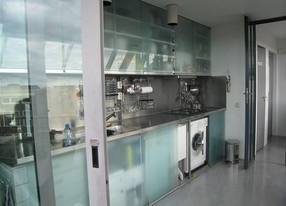 Za posuvnými skleněnými dvířky se skryla v kuchyni i pračka.