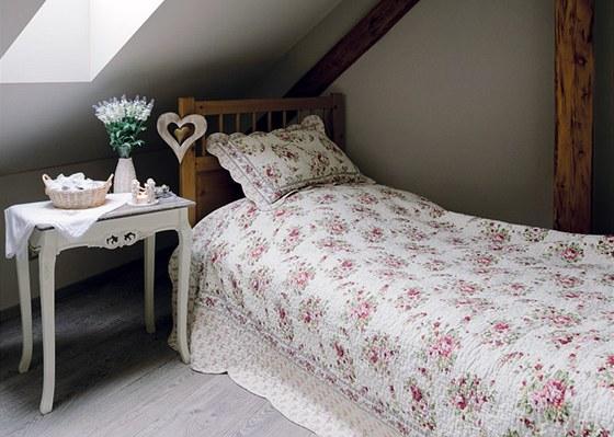 V ložnici pro hosty je přes postel z IKEA přehozen květovaný prošívaný přehoz